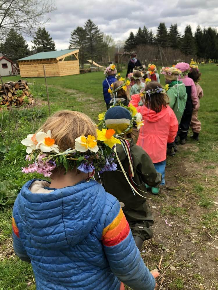 Children from the Pumpkin Patch kindergarten head out to the Maypole wearing flower crowns made that morning.